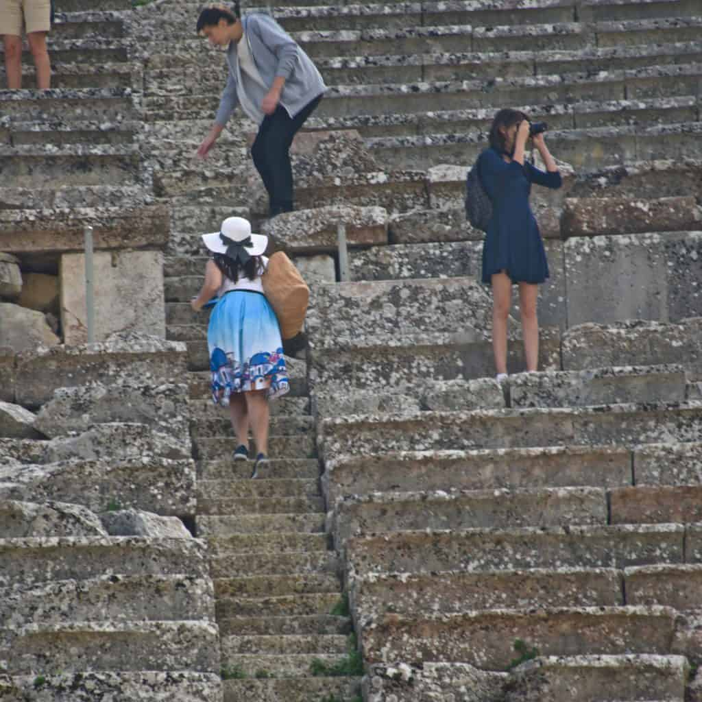 Tourists scattered on the theater steps.