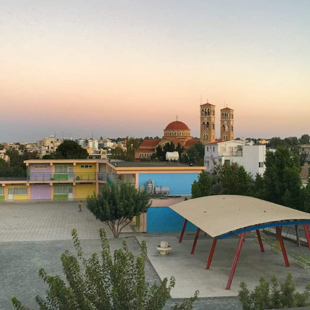 Even though the sun isn't in the photo, the natural light created at sunset makes the scene of the Orthodox church and the school warmer and more colorful. From my trip to Nicosia, Cyprus in September. (Nikon D810)