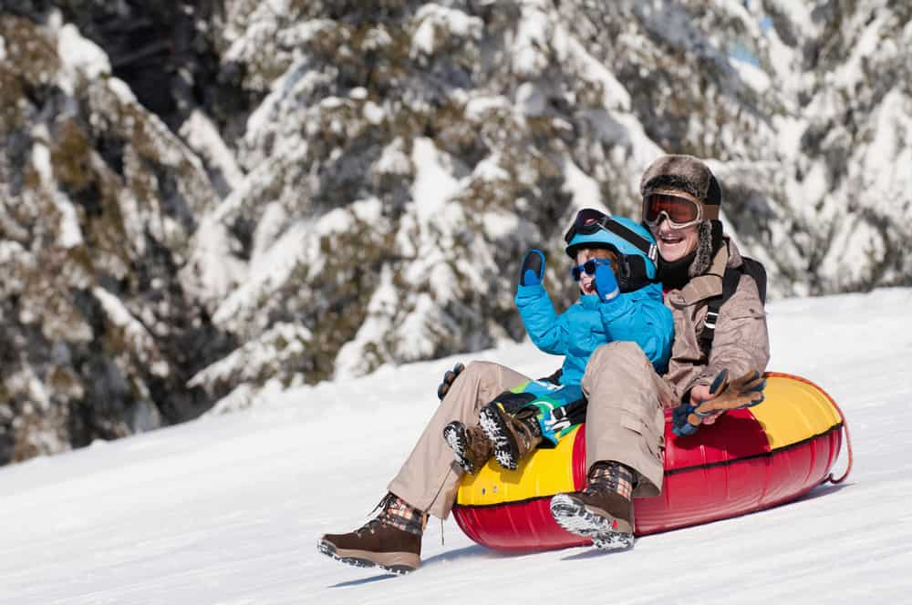 Andorra - Young woman and child sliding down in inflatable snow tube