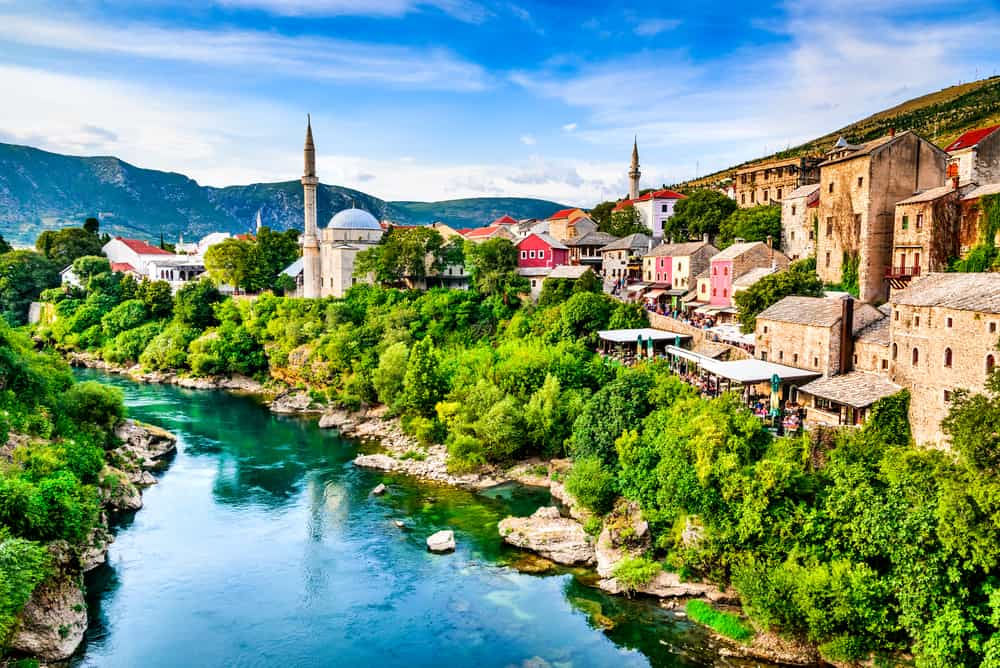 Mostar, Bosnia and Herzegovina. Morning sun on Nerteva River and Old City of Mostar, with Ottoman Mosque