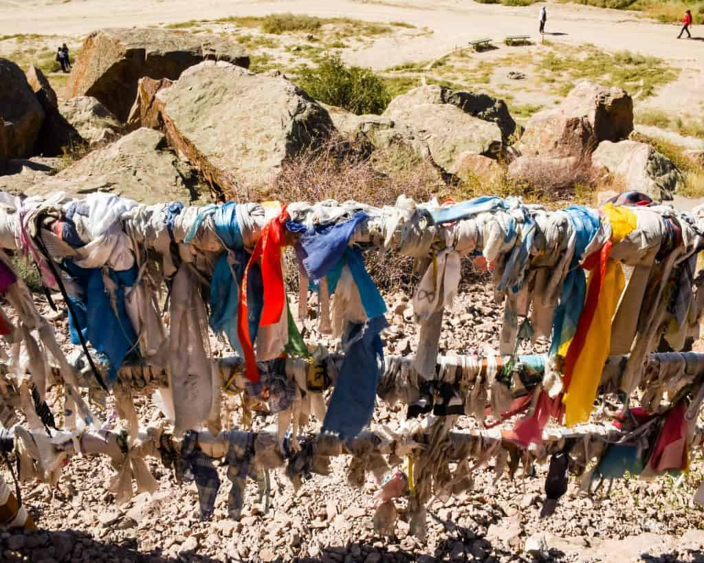 Buddhist prayer flags in front of the main petroglyphs at Tamgaly Tas