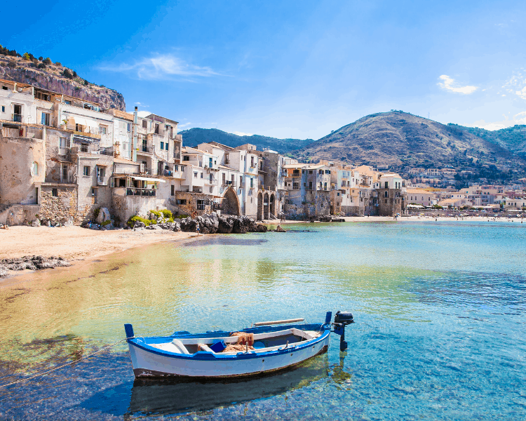Italy - Sicily - a boat in the water with houses