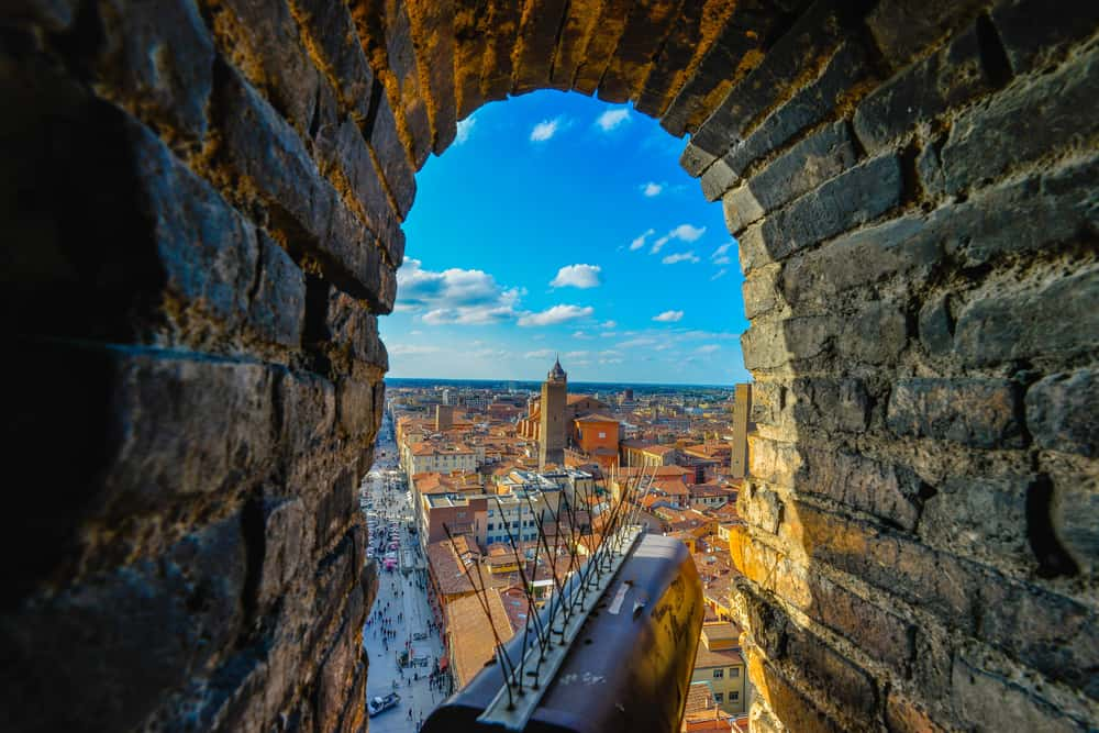 Views from Garisenda tower in Bologna, Italy throug a window to he city center with a surveillance camera in the foreground and the bricks of the tower as the natural frame
