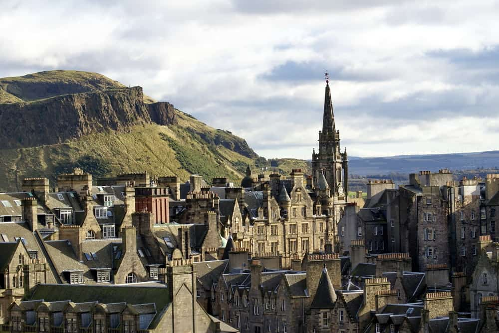 UK - Scotland - Edinburgh, Scotland Old Town, with the spire of The Hub protruding above the roof line and the Firth of Forth in the distance, seen from above - Image