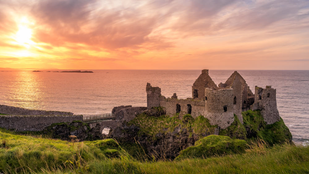 UK - Northern Ireland - Ruined medieval Dunluce Castle on the cliff at amazing sunset, Wild Atlantic Way, Bushmills, County Antrim, Northern Ireland. Filming location of popular TV show, Game of Thrones, Castle Greyjoy