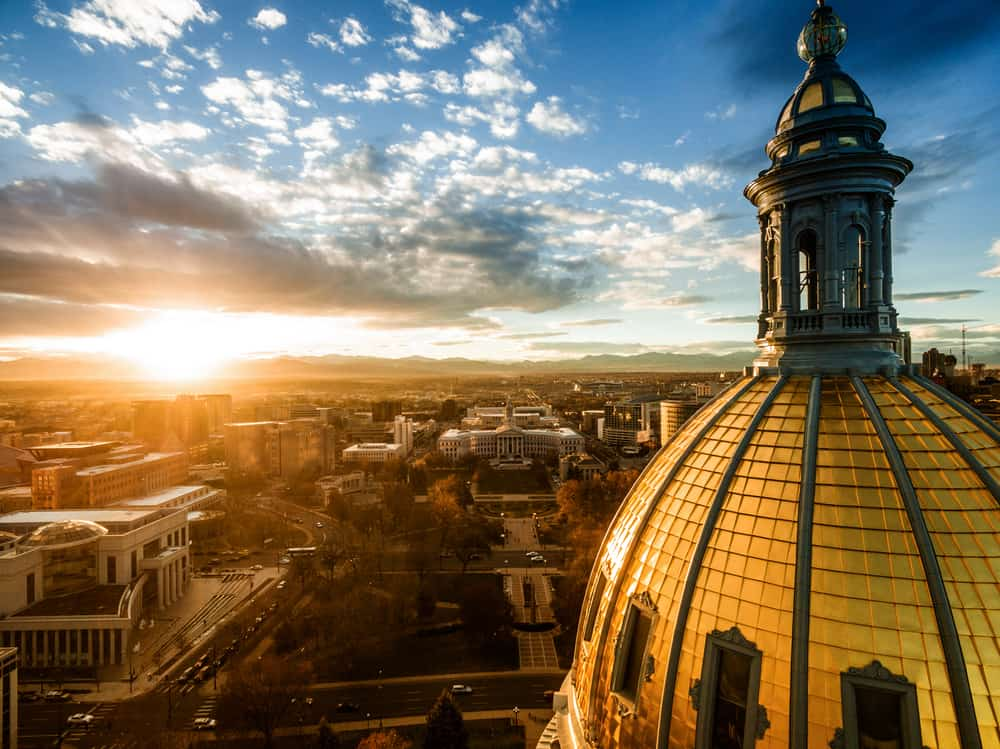 USA - Colorado - Aerial/Drone photograph of a sunset over the Colorado state capital building. Capital city of Denver. The Rocky Mountains can be seen on the horizon