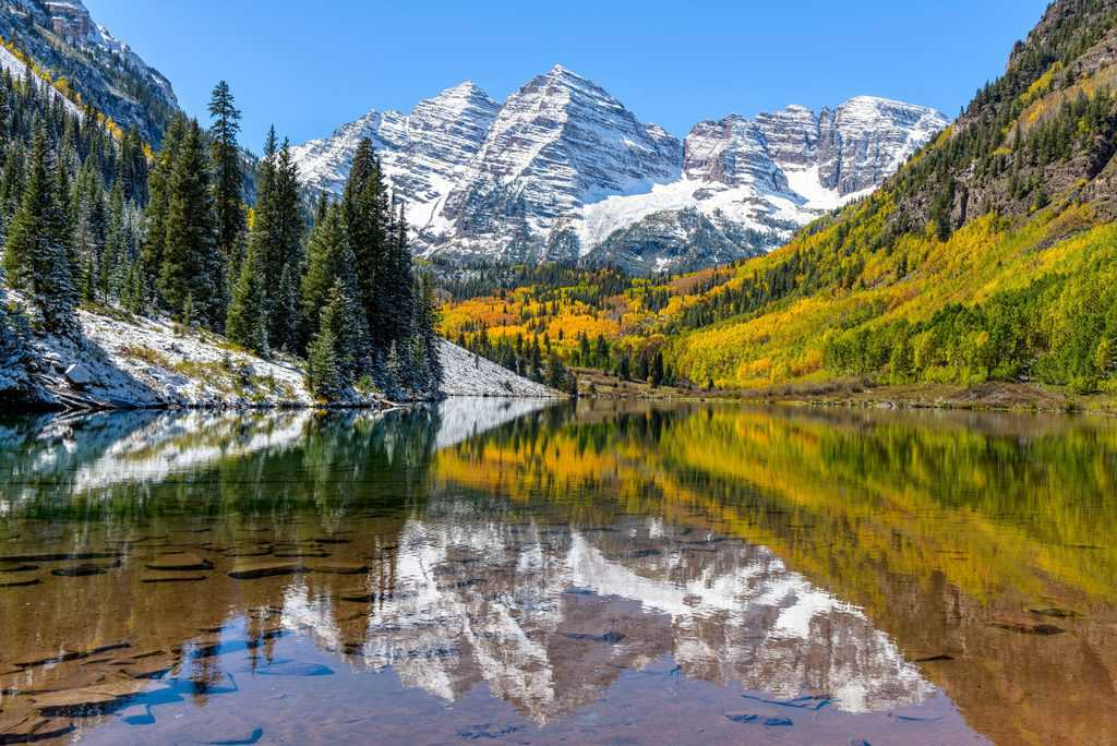 USA - Colorado - Maroon Bells and Maroon Lake - A wide-angle autumn midday view of snow coated Maroon Bells reflecting in crystal clear Maroon Lake, Aspen, Colorado, USA.