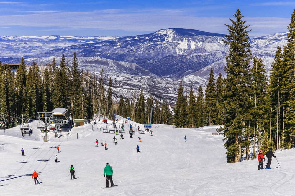 USA - Colorado - View of a Colorado ski resort on a nice winter day; skiers and snowboarders skiing down the slope to the base of a chairlift; trees and mountains in the background