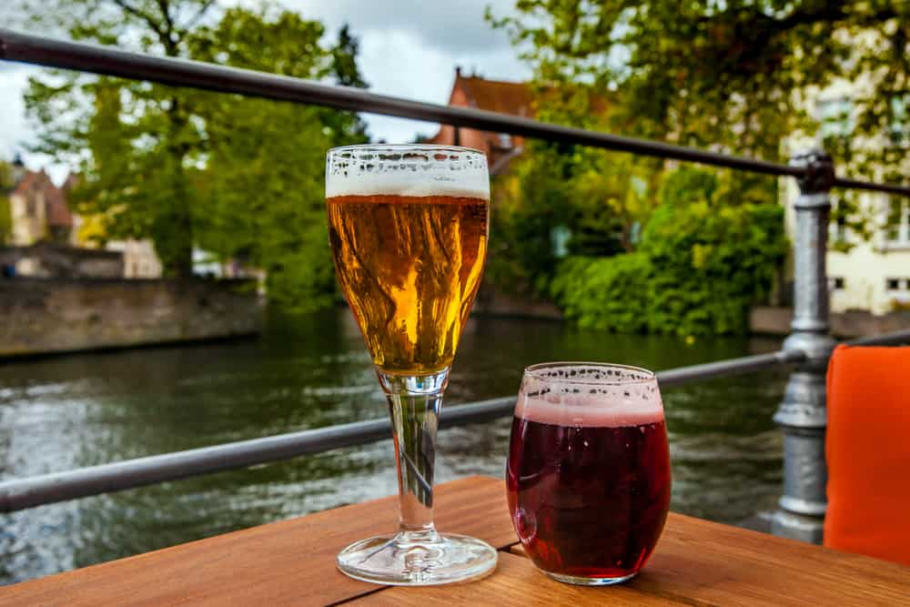 Belgium - Two glasses of belgian beer standing on the table with Bruges city view