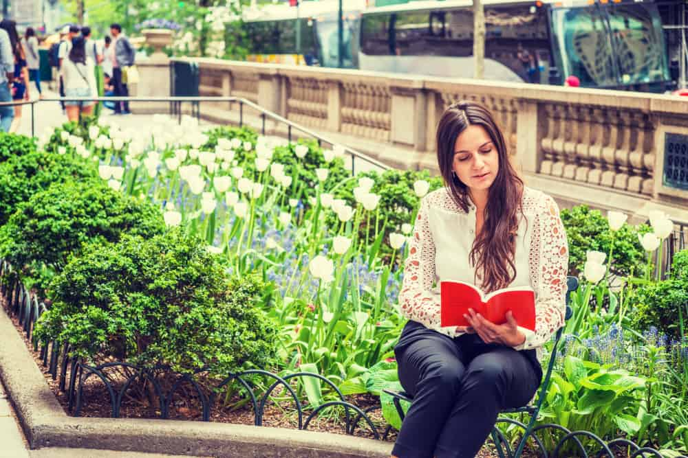 USA - New York - I love reading. Young Eastern European Woman with long hair, wearing white, lace cut out long sleeve shirt, sitting by flowers at street park in Middletown of Manhattan, New York, reading red book.