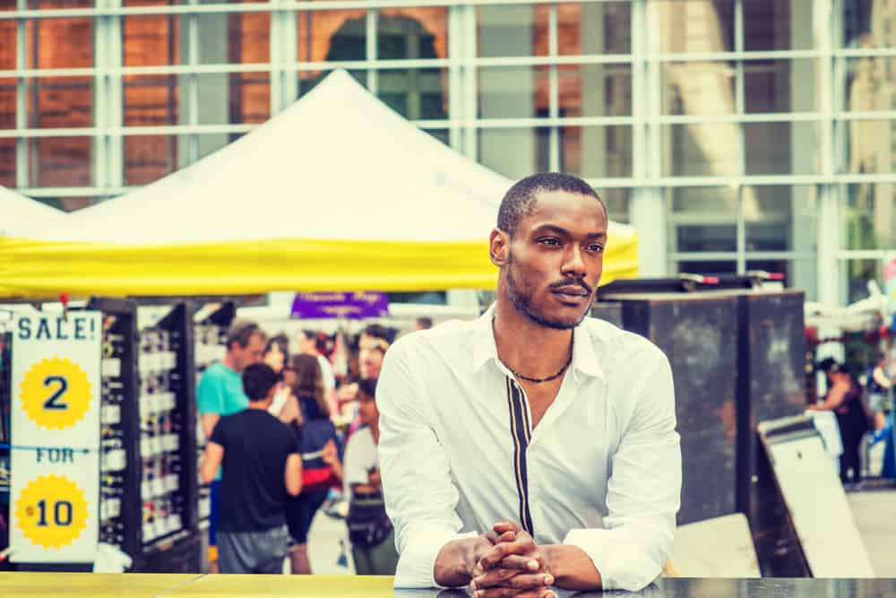 USA - NEW York - Summer Street Fair and Flea Market in New York. Young African American Man shopping, traveling in New York, wearing white shirt, standing on street in Midtown of Manhattan, thinking, lost in thought.