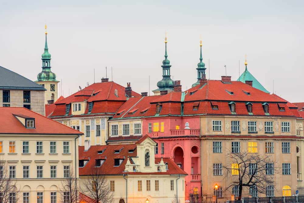 Close view on historical center of Prague with red tile roof houses and green domes with spires of Clementinum architectural complex early in the morning. View from Manesuv Bridge.