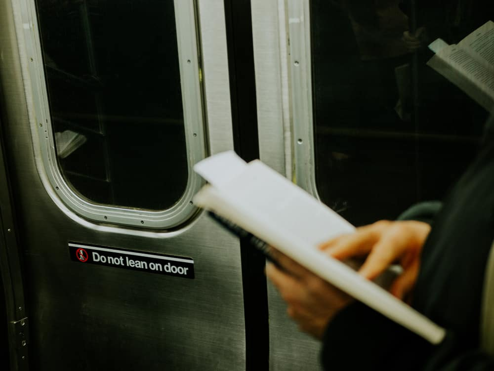 USA - New York - Man reading book in New York subway. Focus on the door train
