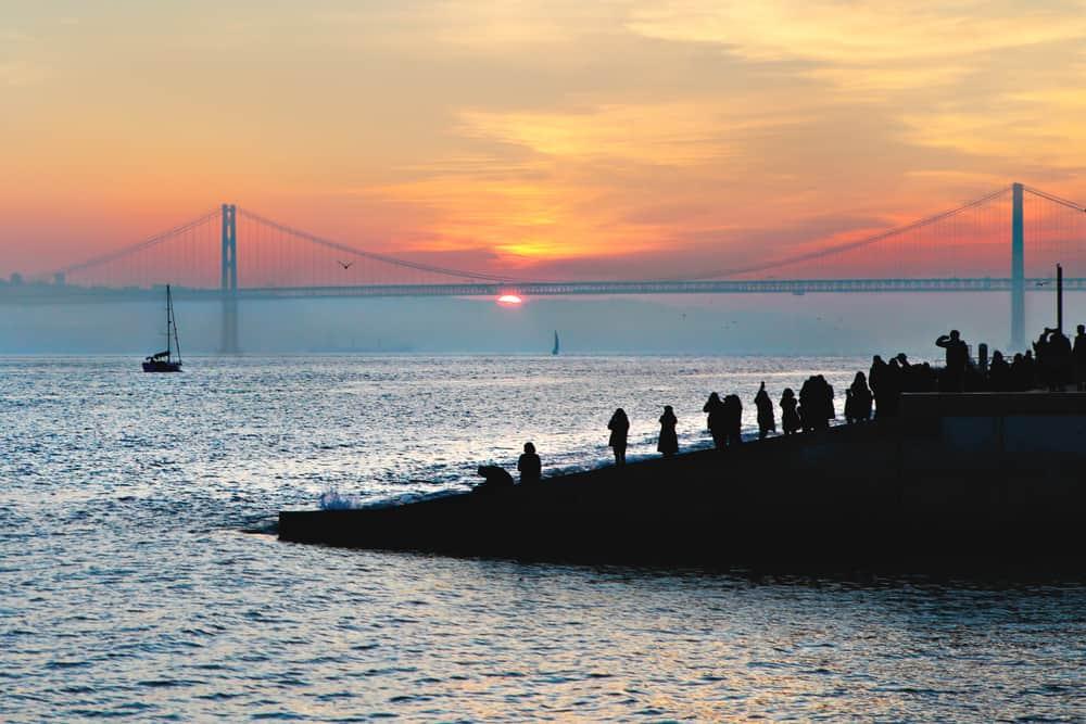 People admiring the 25th of April Bridge at sunset, Lisbon, Portugal
