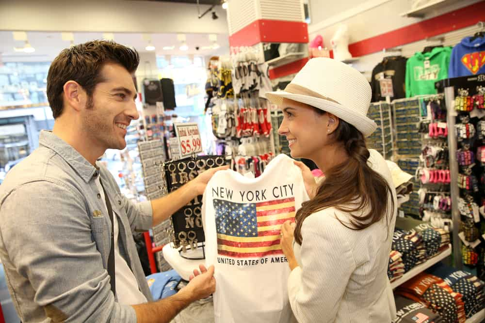 USA - New York - Couple of tourists in gift shop buying a shirt of New York City