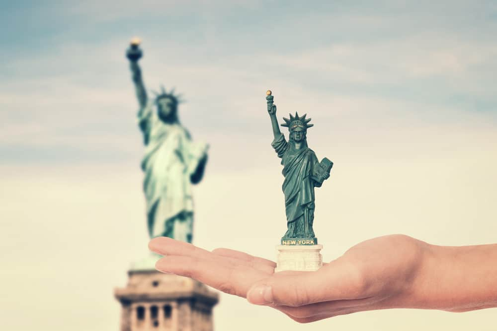 USA - New York - Hand holding a Statue of Liberty souvenir toy, real Statue of Liberty in the background, New York, USA