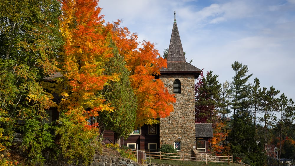 USA - New York - A stone church steeple surrounded by colorful autumn foliage on a sunny fall day in the village of Lake Placid, New York