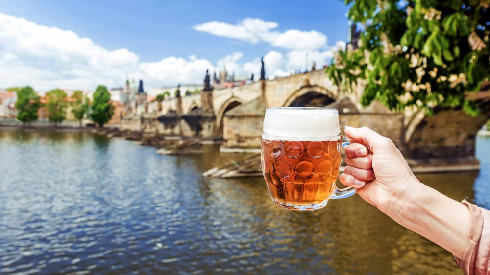hand with a mug of the Czech beer against the background of Charles bridge in Prague