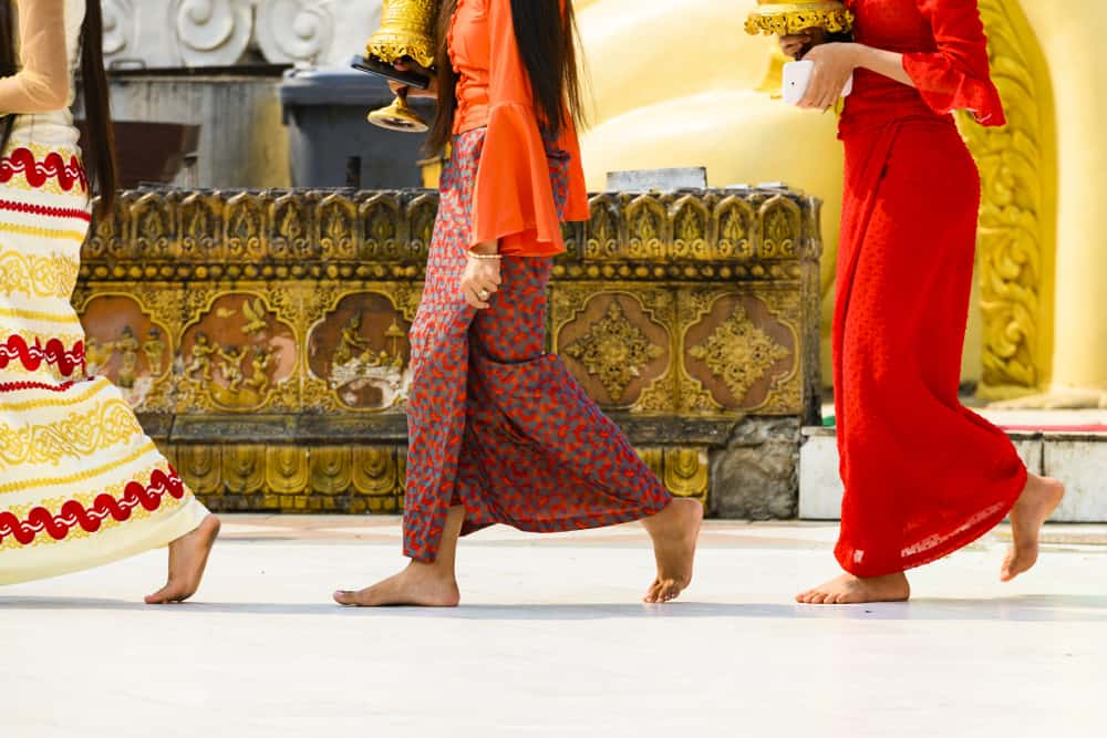 Some Burmese Buddhist faithful are walking barefoot around the Shwedagon Pagoda wearing a traditional and colorful Longyi (traditional Burmese clothes). Yangon, Myanmar.