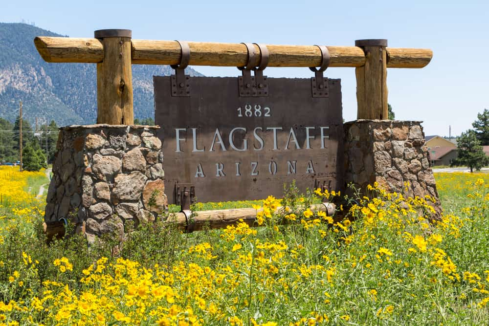 USA - Flagstaff - Entering sign Flagstaff in a mountain landscape with yellow flowers