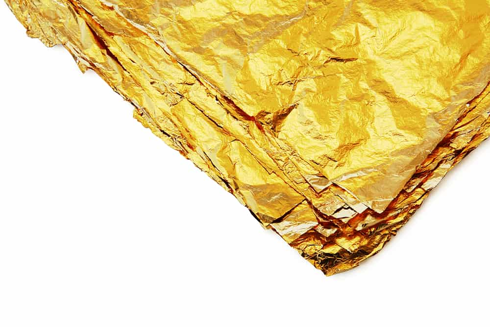 pile of gold sheets on a white background
