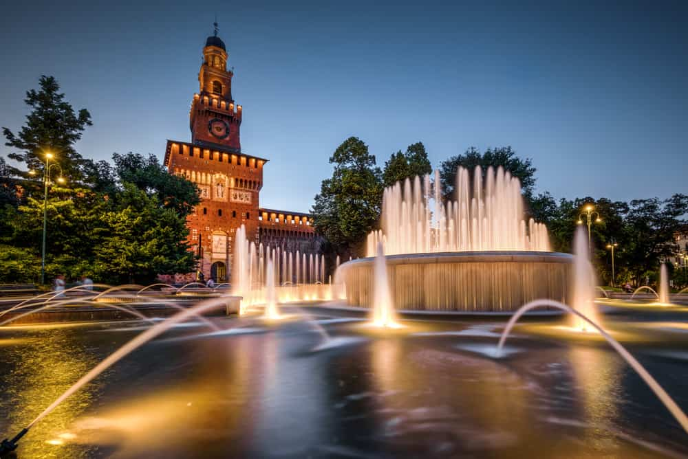 Sforza Castle (Castello Sforzesco) with beautiful fountain at night, Milan, Italy. This old castle was built by Sforza, Duke of Milan. It is one of top landmarks of Milan. Nice tourist place at dusk.