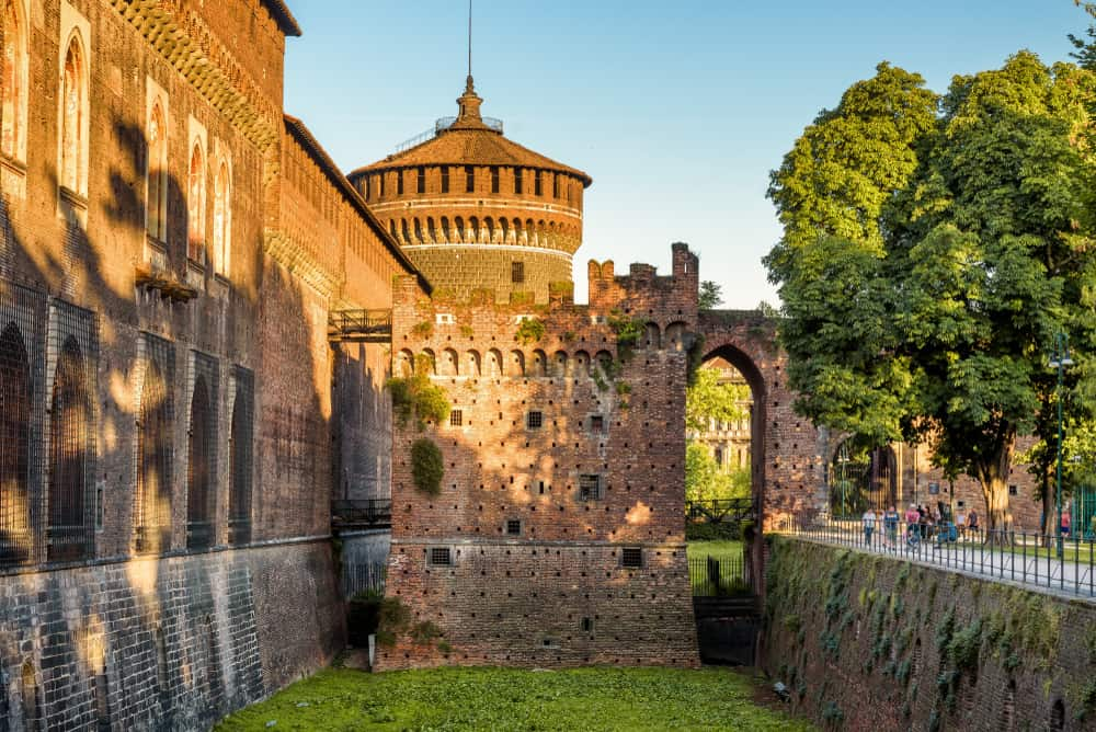 Sforza Castle (Castello Sforzesco) with moat in summer, Milan, Italy. This old castle was built in 15th cent by Francesco Sforza, Duke of Milan. Historical architecture and famous landmark in Milan.