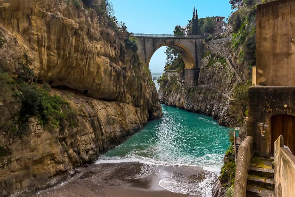 A turquoise sea rushes up the beach at Fiordo di Furore on the Amalfi coast, Italy