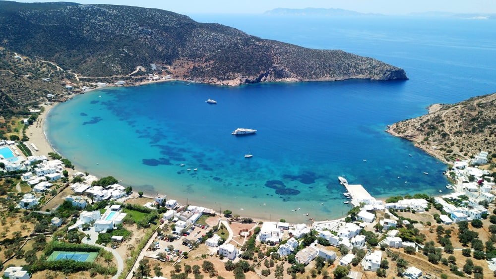 Aerial drone bird's eye view photo from famous and picturesque bay and fishing village of Vathi with iconic whitewashed church of Taxiarhis and turquoise clear waters, Sifnos island, Cyclades, Greece