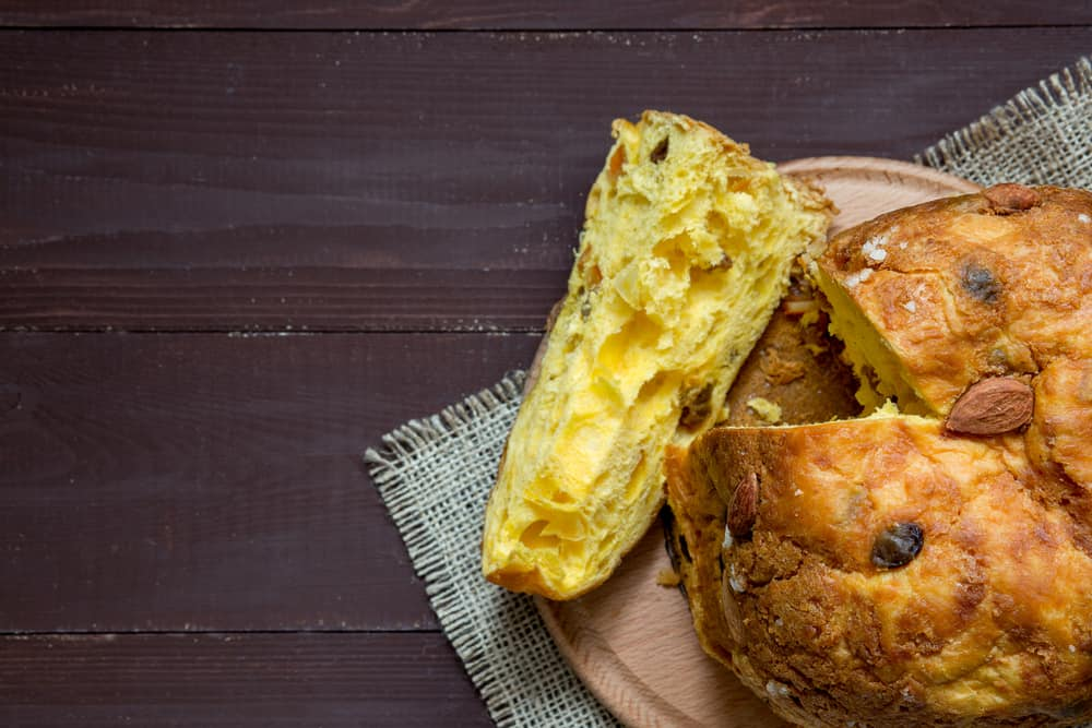 Slices of panettone with fruits and nuts, italian Christmas dessert, background, copy space