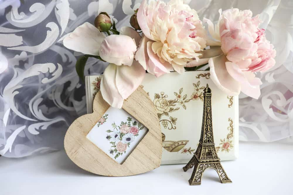 romantic composition. Eiffel Tower figurine, pink peonies, box and envelope
