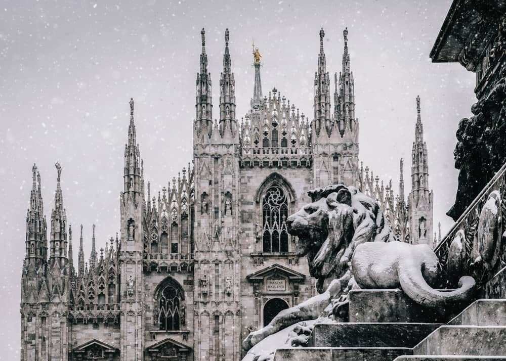 Snow falling on a statue of a lion with the Milan Cathedral in the background. The iconic golden statue of the Virgin Mary, Madonnina standing proudly atop the cathedral