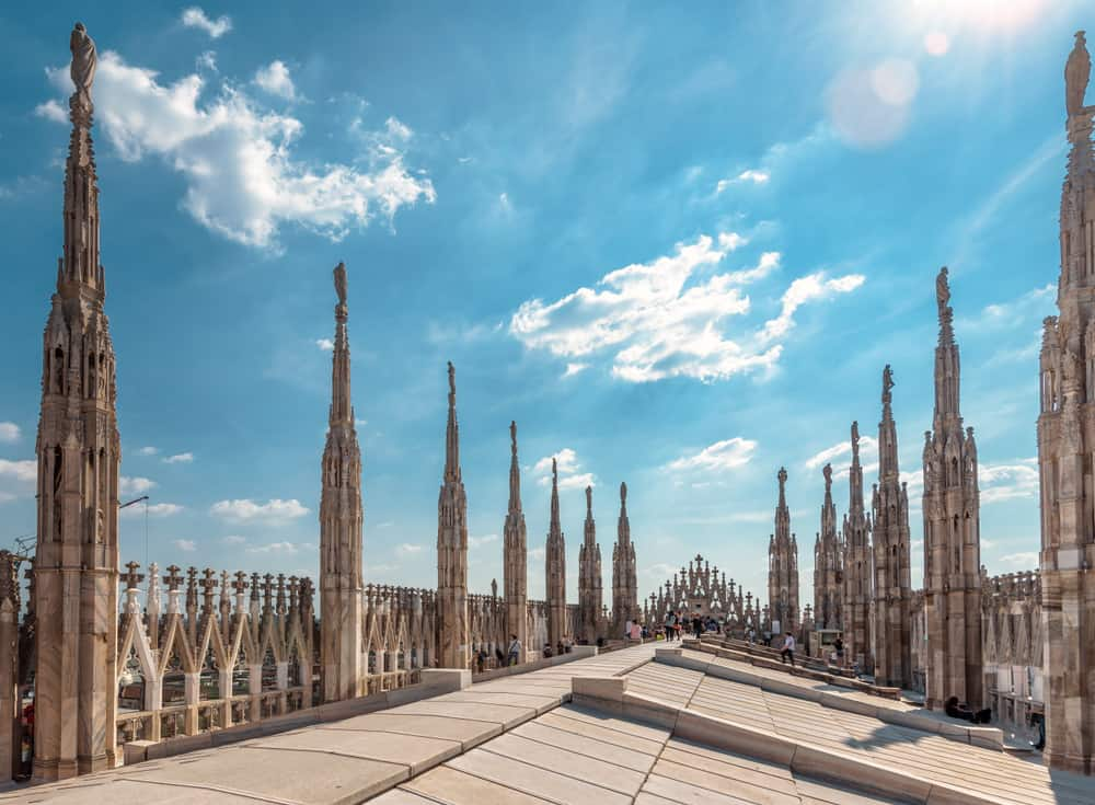Milan Cathedral roof on sunny day, Italy. Milan Cathedral or Duomo di Milano is top tourist attraction of Milan. Amazing view of old Gothic spires. Nice rooftop terrace of the famous Milan landmark.