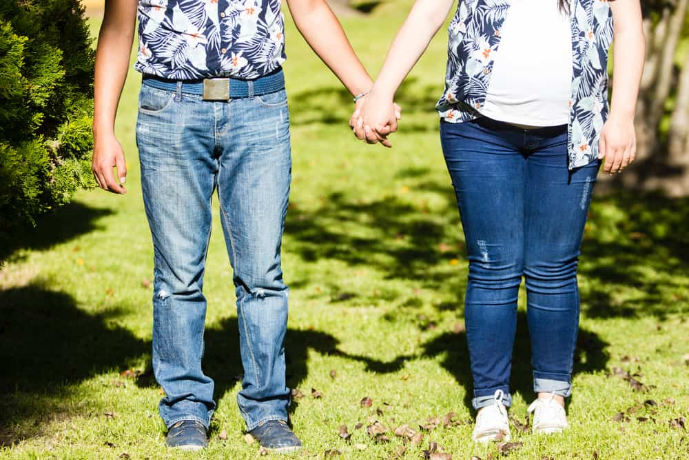 Couple holding hands wearing matching outfit jeans and blue shirt