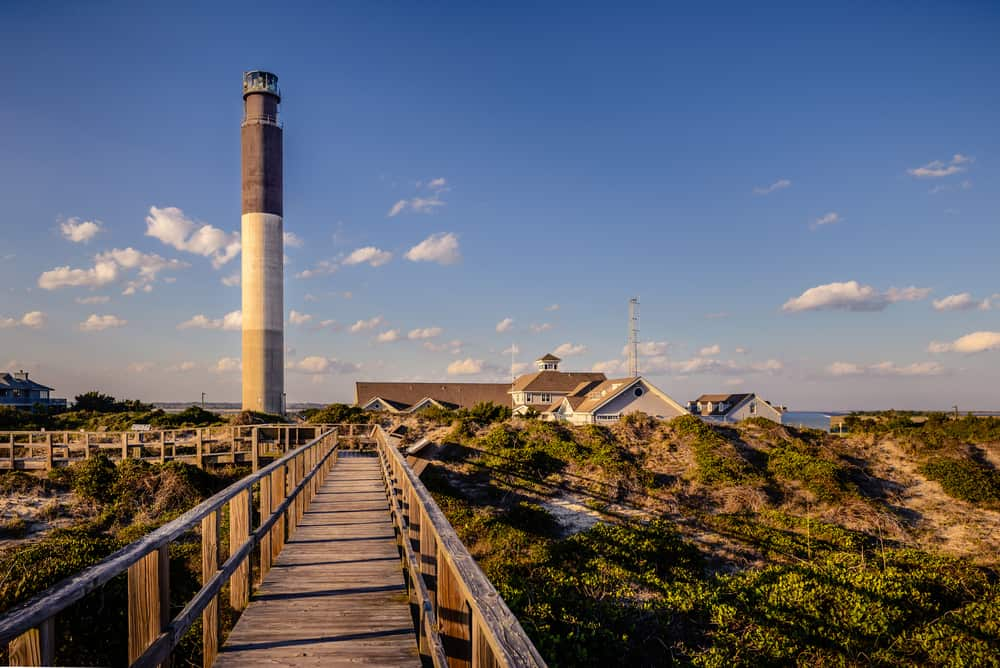 A walking ramp that leads the view to a majestic lighthouse in Oak Island Beach in North Carolina. This image was taken during a sunny afternoon in spring season.