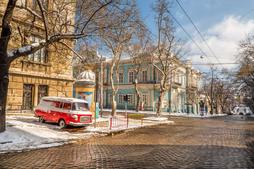 The street of the city is covered with old paving stones and an old car on the roadside. Ukraine. Odessa. Retro car, old historic buildings. Frosty sunny day.