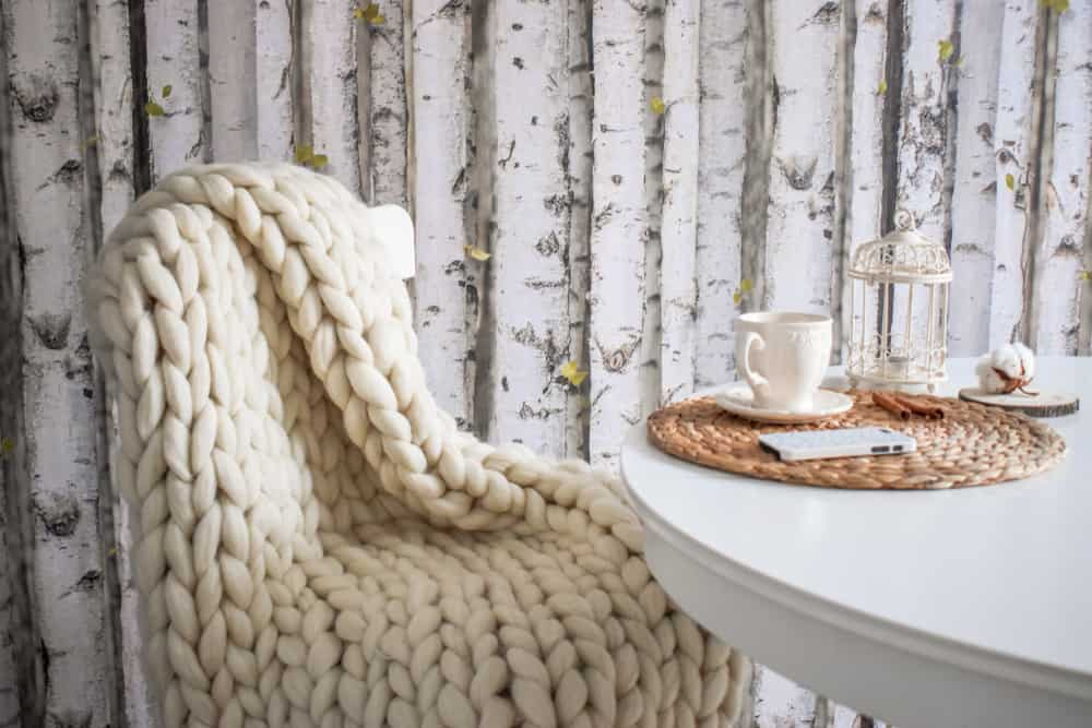 Merino wool handmade knitted blanket on a chair near the table with cup