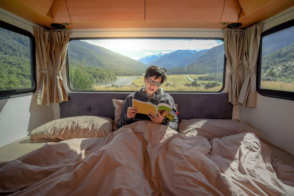 Young Asian man staying in the blanket reading magazine book in camper van with mountain scenery through the window. Road trip in summer od South Island, New Zealand.