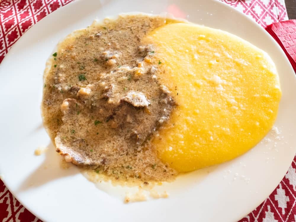 Italy - Milan - Italian cuisine - top view of Manzo all'Olio (beef stew in oil sauce) with polenta on white plate in local restaurant in Lombardy