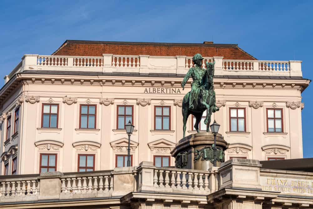 Austria, Vienna, Albrechtsplatz: Front view of world famous Albertina museum palais palace with Albrecht statue in the city center of the Austrian capital with blue sky - concept travel history art