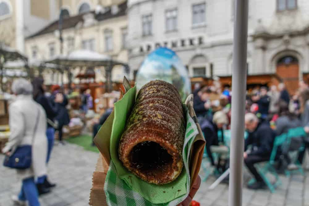 Trdelnik or spit cake sweet dessert as served on an open air food market in Vienna, Austria.Hand holding a Chimney Cake pastry, served with melted chocolate inside and caramelised sugar topping.