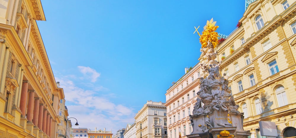 Pestsaule on Graben, famous pedestrian street of Vienna with a Memorial Plague Column. old town main street, autumn travel. Blue skyline. DEO FILIO REDEMPTORI translate as God the Son, the Redeemer