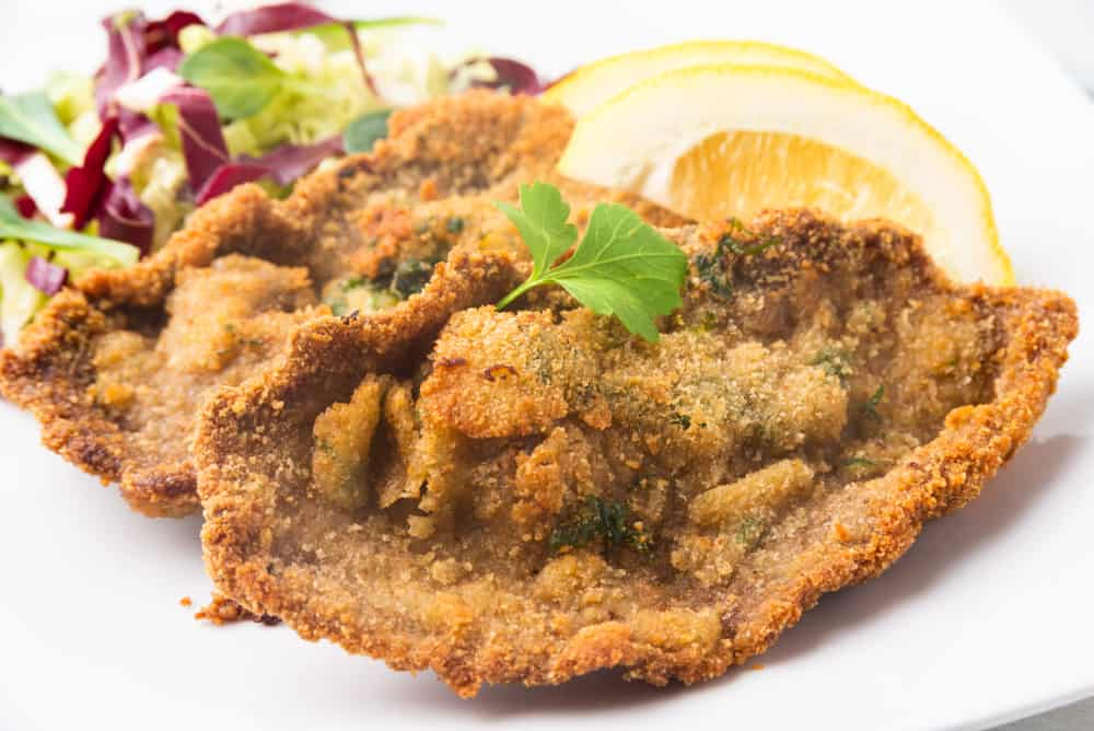 Italy - Milan - Fried beef cutlets with fresh salad, cotoletta alla milanese, typical food from Milano, Italy