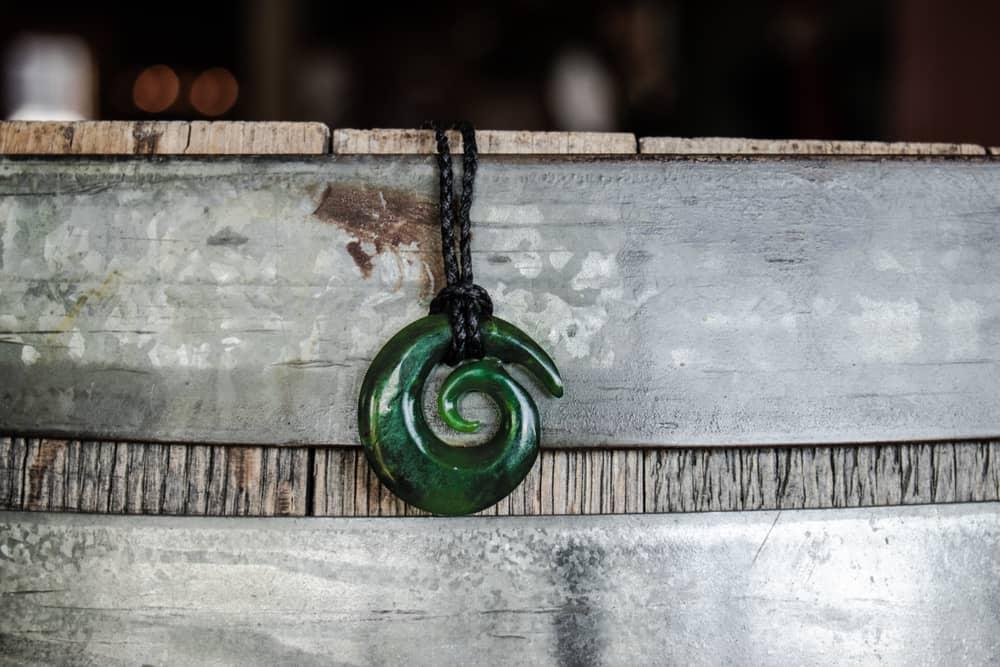 Jade Koru necklace over oak barrel