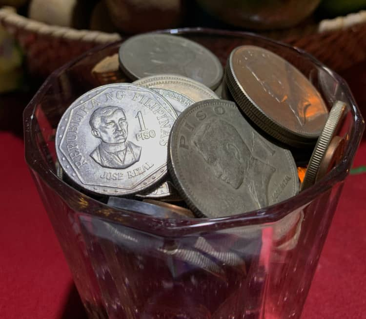 Filipino custom of putting coins on a table beside round fruits, rice and salt for a bountiful New Year