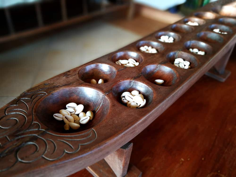 A close-up shot of sungkaan, a pit-carved wooden board. Sungka is a native Filipino game played with seashells or pebbles. It is the Philippine version of mancala.