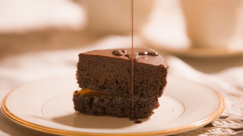 Chocolate sauce being poured over a homemade gluten-free Sachertorte chocolate cake. Served elegantly on a gold and white plate in the dining room of an upscale American home.