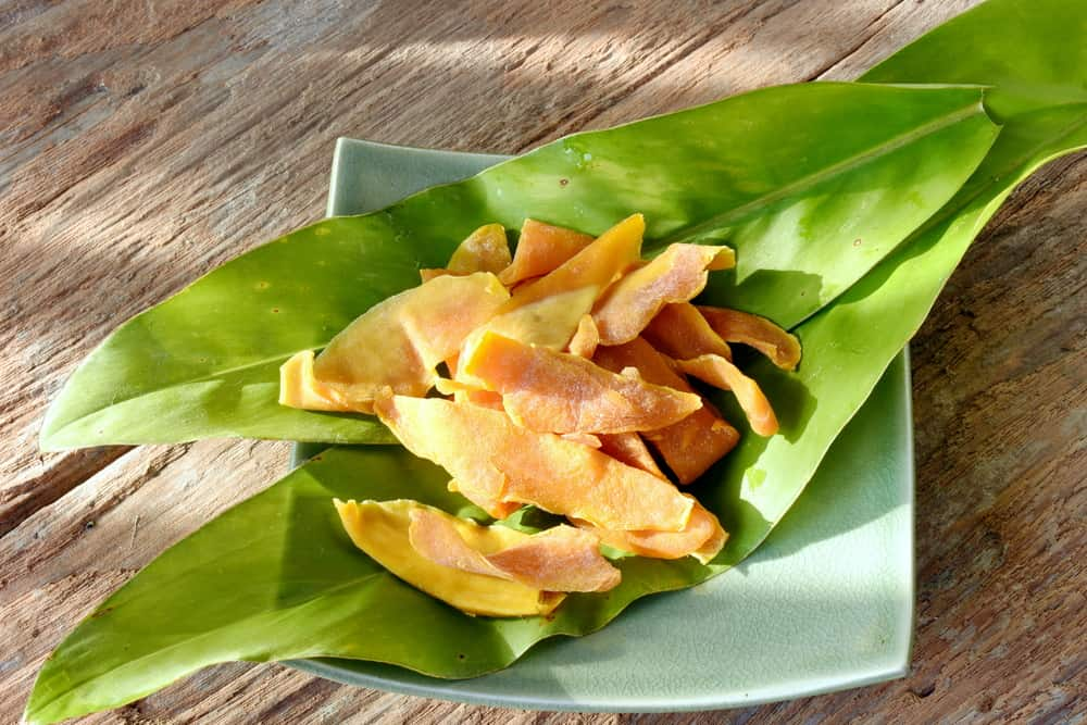 Dried mango from Cebu,Philippines. Preserved mango on green leaves and wood background, shaded with afternoon light, fruit snacks.