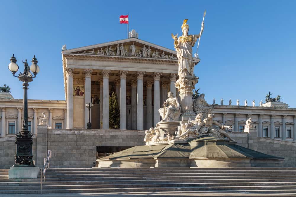 The Austrian Parliament Building in Vienna, Austria, located on The Ring Road. The Athena Fountain with a mythical goddess statue in front.