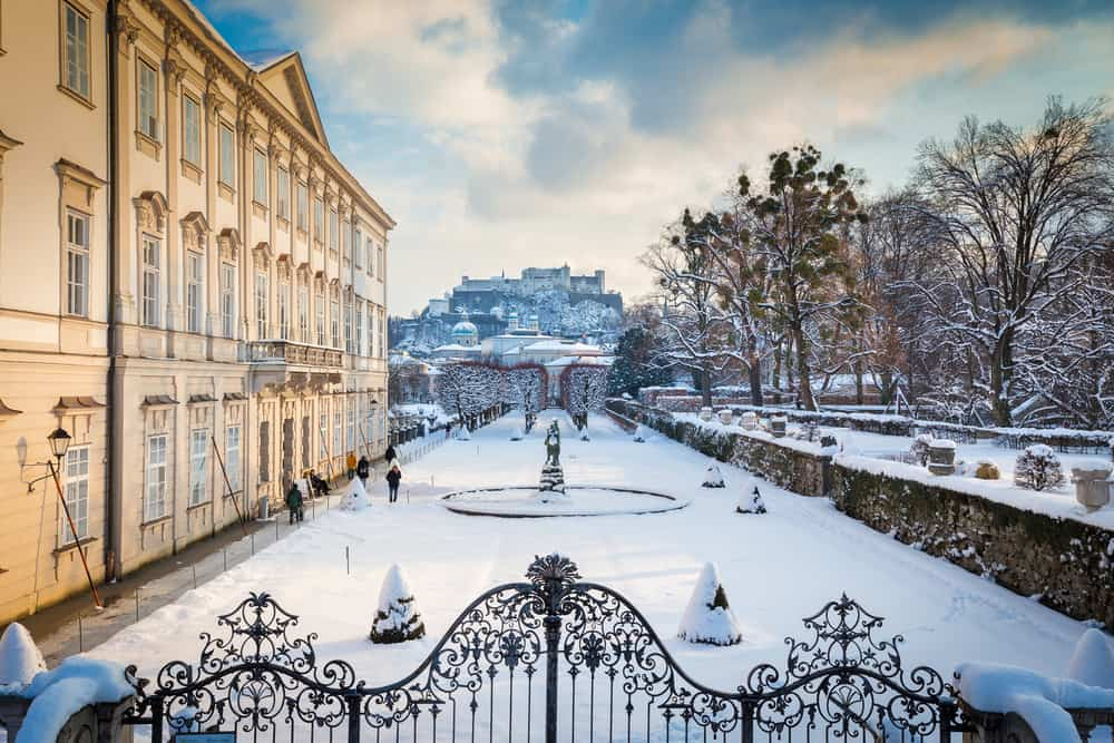 Classic view of famous Mirabell Gardens with historic Hohensalzburg Fortress in the background in scenic golden evening light at sunset on a beautiful cold sunny day in winter, Salzburg, Austria